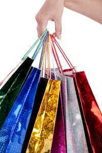 Colorful shopping bags holding by human hand