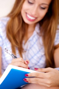 Young woman sitting on sofa writing in notepad