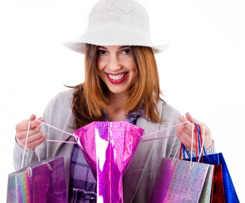 Women showing her shopping bags after her purchase on an isolated white background