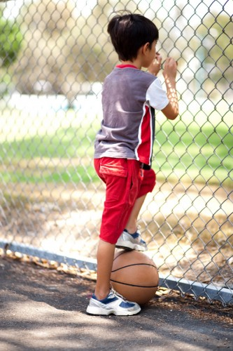 Rear view of young basketball player holding ball under his leg and and looking through fence