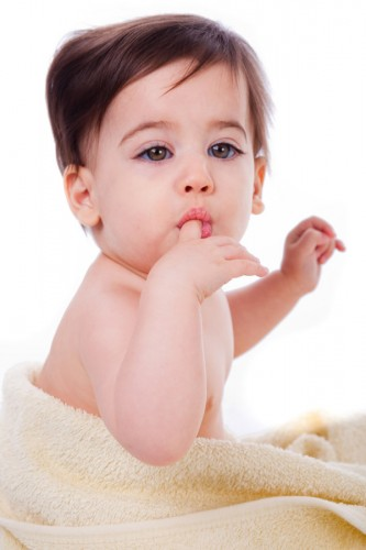 Baby with finger in mouth looking  the camera in a white isolated background