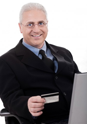 Senior business man making online purchase with his credit card on white background