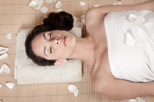 Attractive woman getting flower spa treatment in bamboo mat